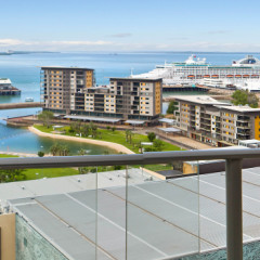 Arkaba glass-railed balcony looking out over Darwin Waterfront Lagoon with cruise liner in Port